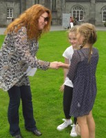 Adult shaking hands with two children